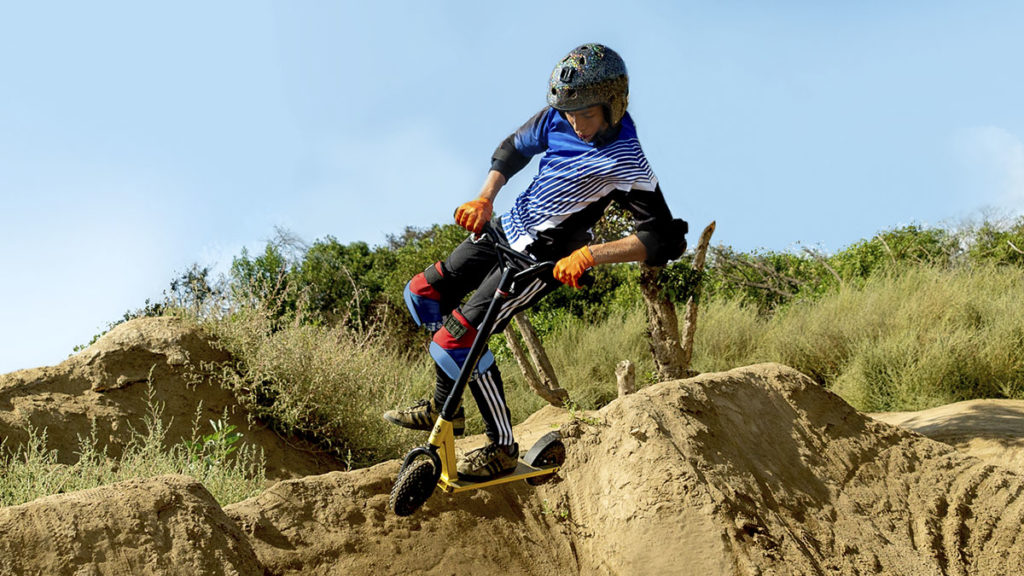 Young man riding the KR-1 dirt stunt scooter on a trail.