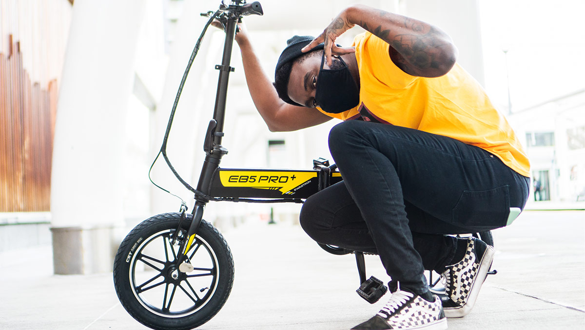 Rossini wearing black pants and yellow shirt squatting next to eb5 pro plus ebike in denver downtown.