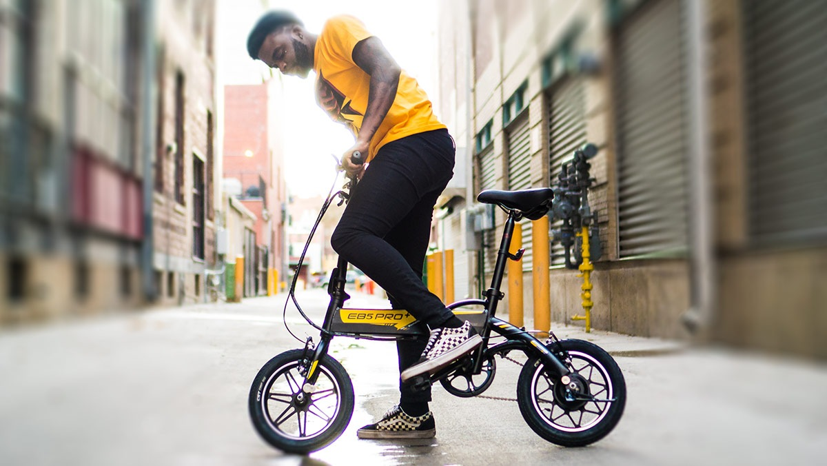 Rossini wearing yellow pants and shirt riding an eb5 pro plus ebike in denver 16th street mall.