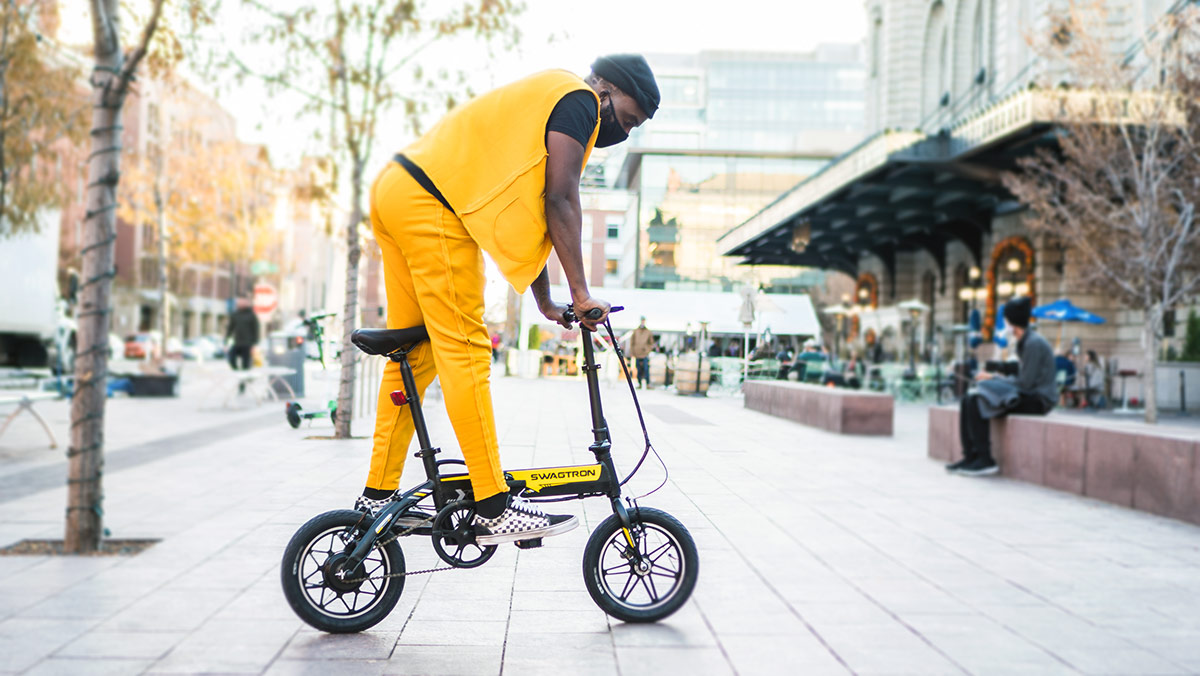 Rossini wearing yellow pants and shirt riding an eb5 pro plus ebike in denver union station.
