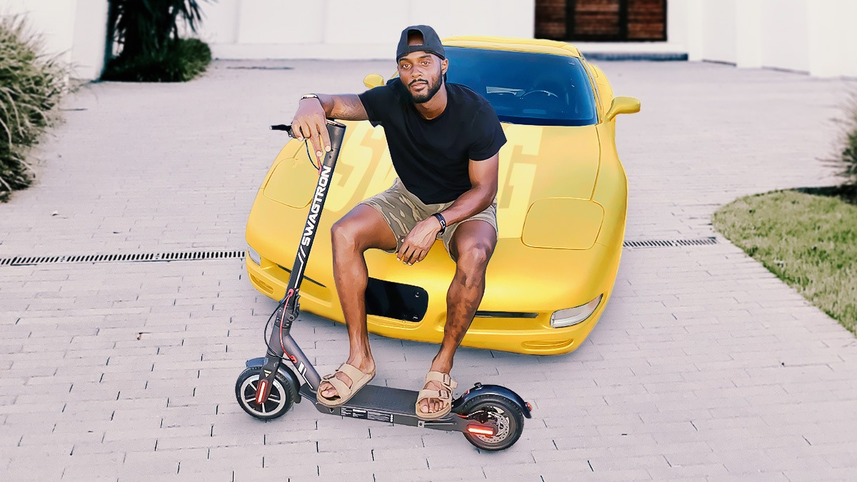Cyril Grayson sitting on car with his Swagger 5 Elite electric scooter.