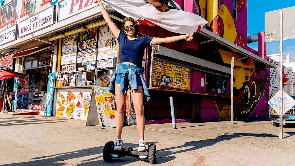 Young woman standing on a swagBOARD T6 hoverboard in front of a store.