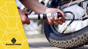 Close-up of man putting air in SWAGTRON eBike tire using an air pump.