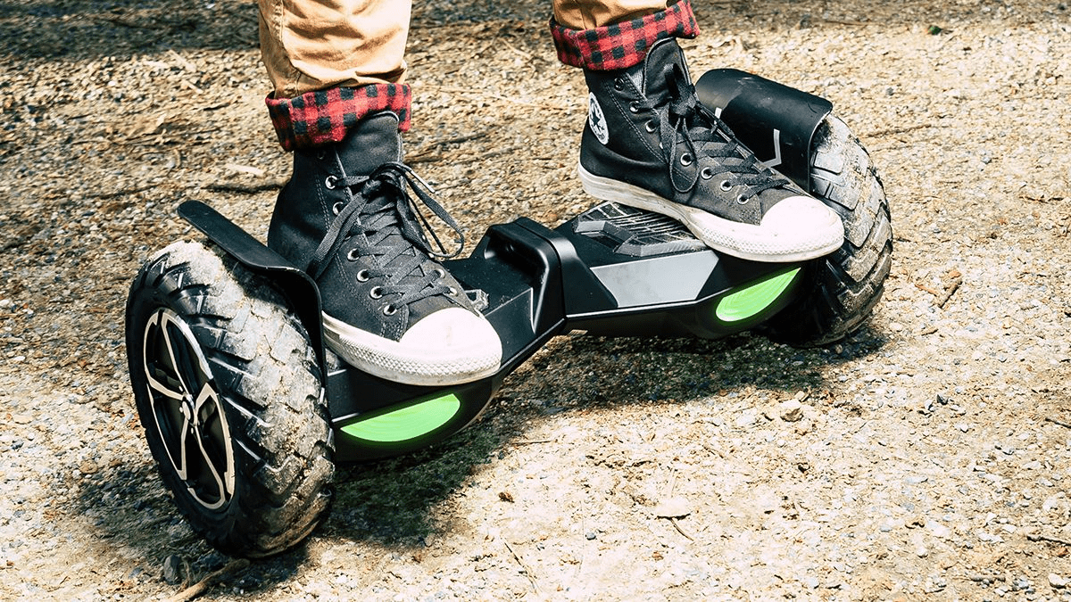Closeup of guy standing on the T6 hoverboard in the dirt.